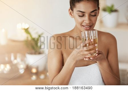 Tender african girl smiling holding glass with tea resting in spa salon. Closed eyes.