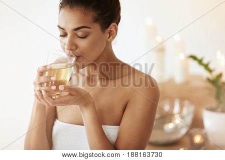 Young attractive african girl drinking green tea resting in spa salon. Closed eyes.