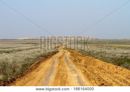 Sand spring steppe road on blue sky background
