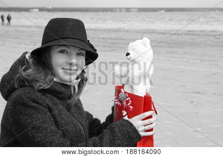 A Young Beautiful Girl In A Hat Sits On The Shore Of The Bay And Is Happy To Receive A Teddy Bear As
