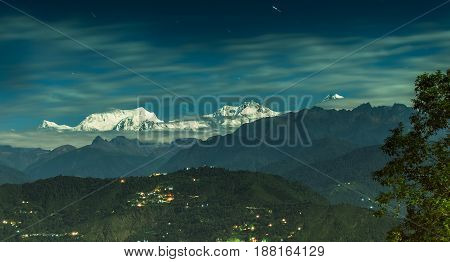 Beautiful panoramic view of moonlit Kanchenjungha Mountain Range of great Himalayas shot in a full moon night. Rinchenpong Sikkim India