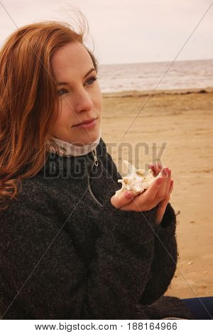Young Red-haired Girl Sits On A Fishing Net And Looks At A Seashell In Her Hands