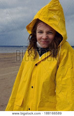 A Beautiful Girl In A Yellow Raincoat Is Standing In The Rain In The Spring On The Shore Of The Bay