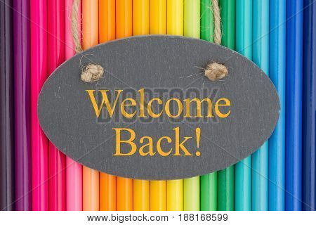 Welcome back text on a chalkboard with colorful pencil crayons