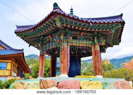 Buddhist Temple with a spirit bell that people can ring from pushing a wooden gong surrounded by a rural forest and mountains