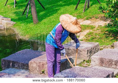 TAIPEI TAIWAN - APRIL 30: This is a typical park cleaner sweeping trash and taking care of the park on a sunny day on April 30 2017 in Taipei