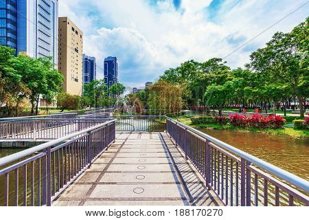 TAIPEI TAIWAN - APRIL 30: Footbridge and pond in a park near office buildings in in the Banqiao district on April 30 2017 in Taipei