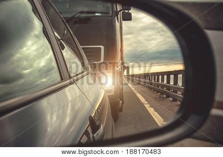 Reflection in the rear-view mirror of the car the cargo with the lights on