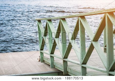 Wooden board on the river pier and the stirring water