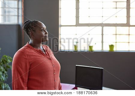 Focused young African businesswoman looking deep in thought while standing alone by windows in a large modern office
