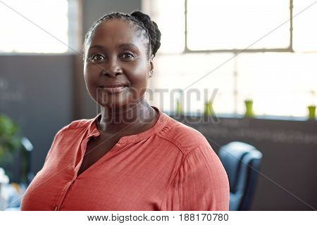 Portrait of a casually dressed young African businesswoman smiling confidently while standing alone in a modern office
