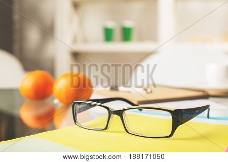 Close up of specs placed and reflected on glass table with blurry supplies and other items. Vision concept