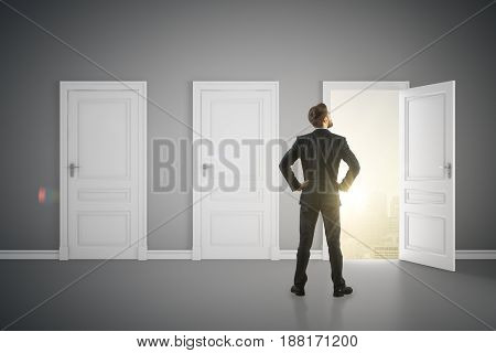 Back view of young businessman in concrete interior looking out of open door with sunlit city view. Success concept. 3D Rendering