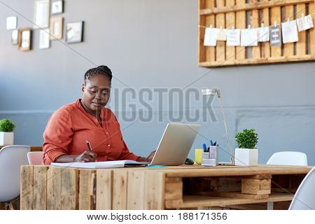 Young African businesswoman working on a laptop and writing down notes in a book while working at her desk in a large modern office