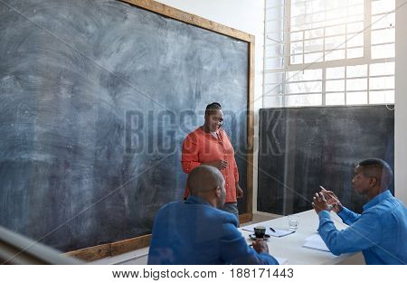 Focused and confident young African businesswoman talking to colleagues while giving a presentation on a chalkboard in a modern office