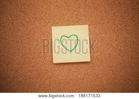 Close up shot of a heart note on a cork board.