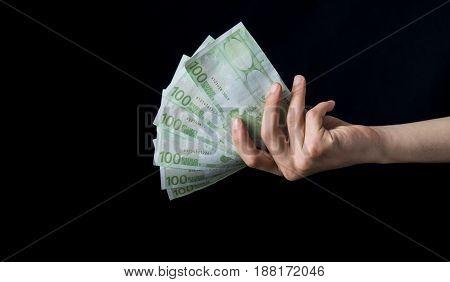 Isolated 100 Euro Cash Holding On A Black Background.