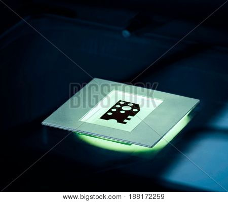 Nano technology concept background. Micro chip matrix illuminated on a microscope table in blue tone.