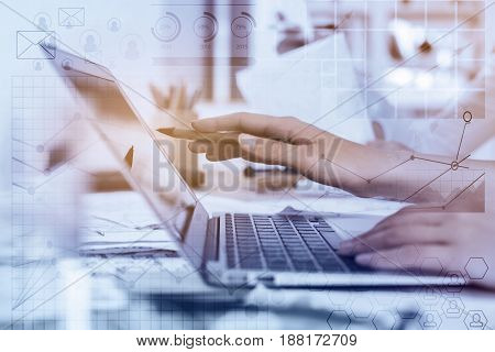 Side view of female hands using laptop at workplace with abstract business pattern. Toned image. Accounting concept