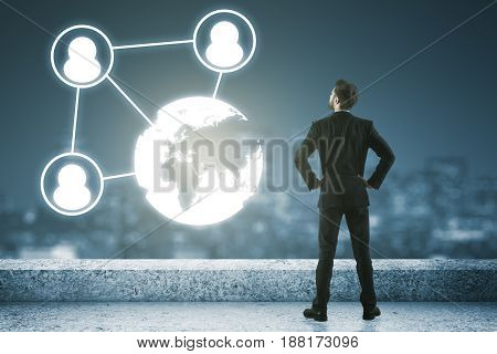 Back view of young businessman standing on rooftop with digital globe chart and night city view. HR concept poster