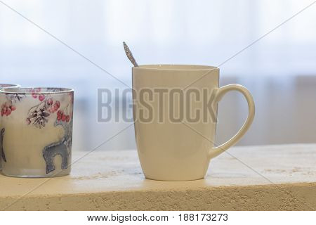 white mug is on the shelf in the interior of flat