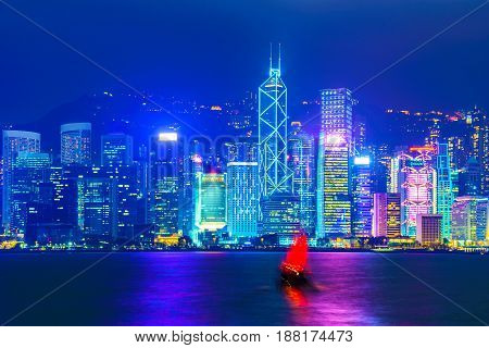 Hong Kong Skyline nigh view with traditional sailboat