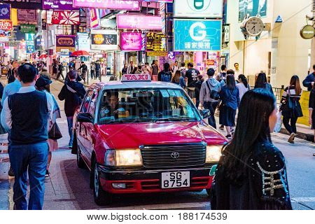 HONG KONG CHINA - APRIL 24: Mong Kok street scene at night with neon signs and a taxi waiting at a traffic light on April 24 2017 in Hong Kong