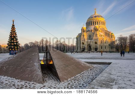 Revolutionary memorial - quenchless flame at Yakornaya square and Orthodox Naval cathedral of Saint Nicholas in Kronshtadt Saint Petersburg Russia