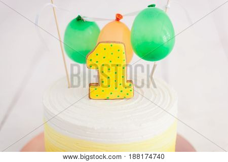 first birthday smash the cake. The cake with number one and little ballons. birthday greetings. Yellow polka dot cookie and cream.