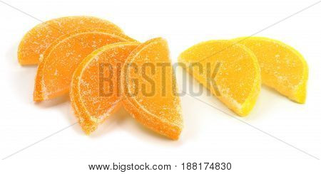 Orange and yellow marmalade in the form of lemon and orange candied slices isolated on white background.