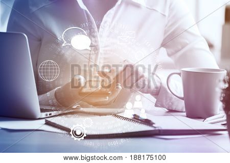 Young woman using cellphone with digital pattern at workplace with laptop paperwork and coffee cup