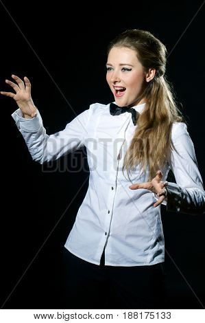 young pretty female shouting at somebody isolated on black background