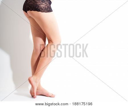 Sexy legs in black panties isolated over white background