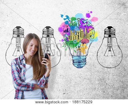 Portrait of young european woman using smartphone on concrete background with business sketch and lamps. Idea concept
