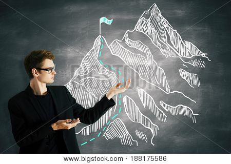 Young businessman presenting business sketch on chalkboard. Way to success concept