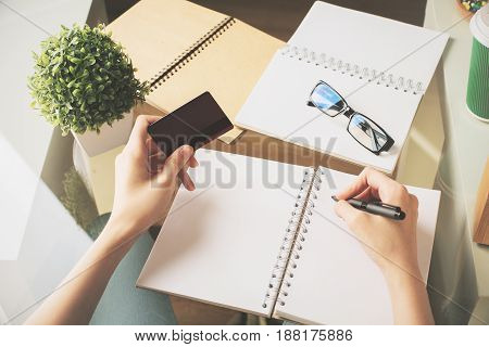Girl copying information from credit/debit card to spiral notepad. Copy space. Close up