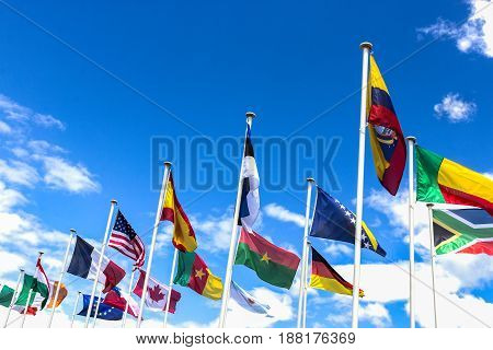 Flags of the different countries against blue sky. Lourdes, France