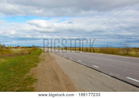 Road stretches into distance to infinity against the cloudy blue sky.  Landscape rural road calling in the way. Track layout for car easy in the countryside. Journey to the horizon of the planet.