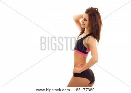 young sexy fitness girl in short shorts stands sideways and posing for the camera isolated on white background