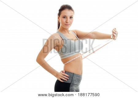 young slim girl in grey top measures waist close-up isolated on white background