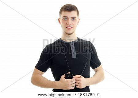 handsome young guy in the black shirt smiling looks straight and holds phone isolated on white background
