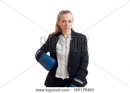 an attractive young girl with a tail stands in shirt and jacket looks straight and keeps a hand on the side of the Boxing Glove isolated on white background.
