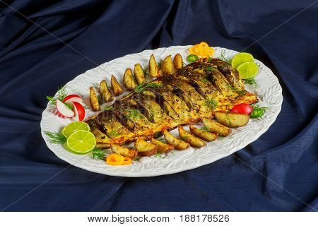 Grilled Fish With Roasted Potatoes And Vegetables On The Plate