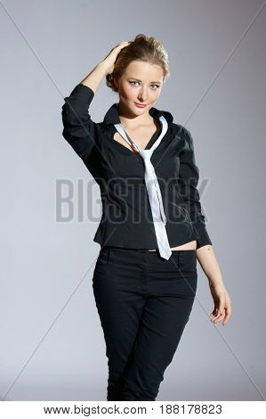 young beautiful charming woman wearing black trousers and black shirt with white necktie