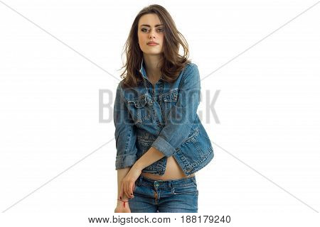 young beautiful brunette smiles and looks into the camera in a jeans jacket close-up isolated on white background