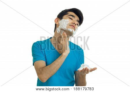 young handsome guy in the blue shirt tilted his head and putting a face shaving foam isolated on white background