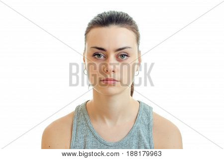 Portrait of a charming young girl without makeup which seriously looks at camera isolated on white background