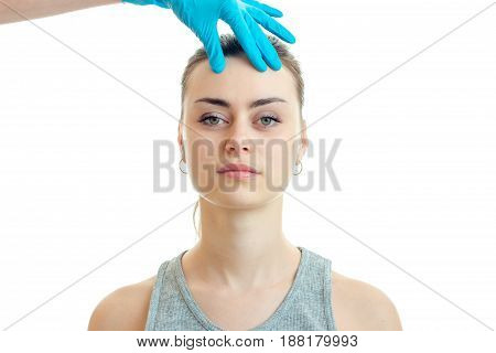 young girl without makeup stands up straight and the doctor in a blue glove touches her face close-up isolated on white background