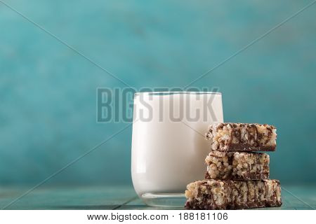 Granola bars and milk on blue background , healthy breakfast