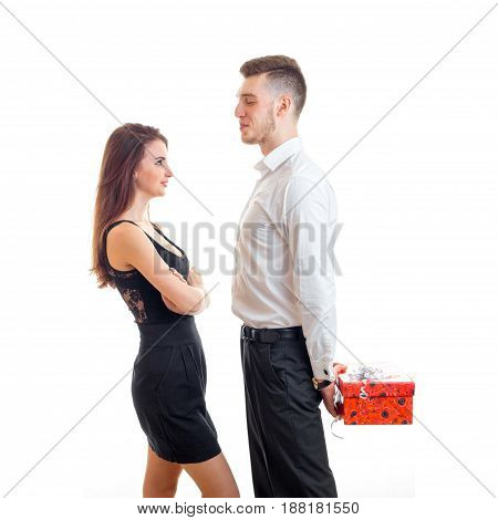 beautiful girl in black dress with a guy in a shirt that keeps behind gift isolated on white background